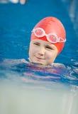 Jeune fille heureuse apprenant à nager dans la piscine Images libres de droits