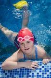 Jeune fille heureuse apprenant à nager dans la piscine avec des nageoires Photographie stock libre de droits