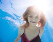 Jeune fille heureuse avec l'eau du fond aux cheveux longs dans la piscine Image libre de droits