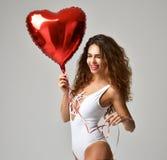 Jeune fille heureuse avec le ballon rouge de coeur comme présent pour le birthda image stock