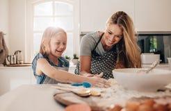Jeune fille heureuse avec sa mère faisant la pâte images libres de droits