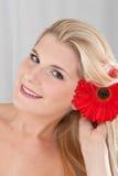Jeune fille heureuse avec une fleur rouge Images stock
