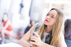 Jeune fille heureuse buvant un cocktail extérieur Image libre de droits