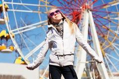 Jeune fille heureuse contre une roue de ferris Photos libres de droits