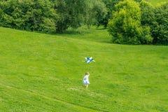 Jeune fille heureuse d'enfant jouant avec le cerf-volant lumineux en parc Photo stock