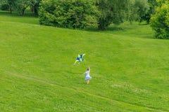 Jeune fille heureuse d'enfant jouant avec le cerf-volant lumineux en parc Photo libre de droits