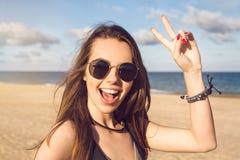 Jeune fille heureuse dans des lunettes de soleil montrant le geste de paix Photo stock