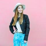 Jeune fille heureuse de blogger de mode posant près du mur utilisant l'équipement occasionnel de style de rue images stock