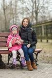 Jeune fille heureuse de mère et d'enfant étreignant se reposer sur le parc de banc au printemps Photo stock
