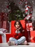 Jeune fille heureuse dedans avec le grand cadeau actuel souriant près du rouge énorme Photographie stock libre de droits