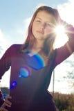 Jeune fille heureuse dehors et éclat du soleil Photographie stock