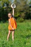Jeune fille heureuse en verres de soleil sautant jouer sur un pré dans le jour ensoleillé Images libres de droits