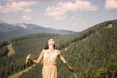 Jeune fille heureuse jouant avec des bulles de savon Photos libres de droits