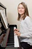 Jeune fille heureuse jouant le piano Images libres de droits