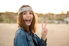 Jeune fille heureuse montrant le geste de paix et regardant l'appareil-photo Photographie stock libre de droits