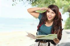 Jeune fille heureuse partant en vacances avec le sac à dos et la carte Photos libres de droits