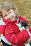 jeune fille heureuse retenant un chaton Image stock