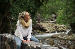 Jeune fille heureuse s'asseyant par les roches dans une forêt appréciant le calme image libre de droits