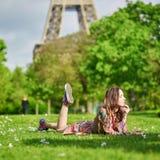Jeune fille heureuse se trouvant sur l'herbe près de Tour Eiffel à Paris Images stock