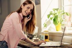 Jeune fille heureuse souriant, parlant au téléphone portable et travaillant sur l'ordinateur portable Photographie stock libre de droits