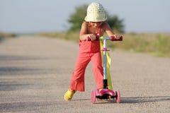 Jeune fille heureuse sur le scooter sur la route Photo stock
