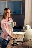 Jeune fille heureuse travaillant sur l'ordinateur portable tout en buvant du café ou du thé Image libre de droits