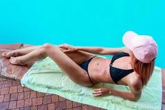 Jeune fille humide prenant un bain de soleil à côté de la piscine, dans le maillot de bain noir Image libre de droits