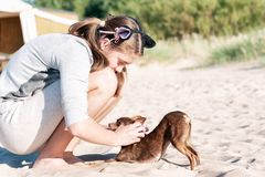 Jeune fille iscratching son beau dos du ` s de chien sur la plage d'été Photo libre de droits