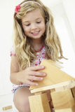 Jeune fille jouant avec les blocs constitutifs en bois dans la chambre à coucher Photo stock
