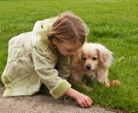 Jeune fille jouant avec un petit crabot image libre de droits