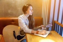Jeune fille jouant la guitare en café images stock