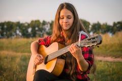 Jeune fille jouant la guitare sur le pré Photographie stock