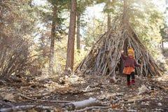 Jeune fille jouant la hutte extérieure faite de branches dans une forêt Photos stock