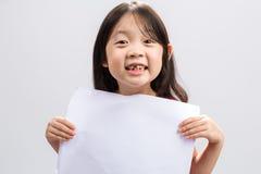 Jeune fille jugeant le papier blanc/jeune fille tenant le fond de papier blanc Images stock