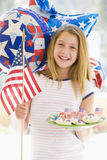 Jeune fille à l'extérieur sur le quart de juillet avec l'indicateur Photographie stock