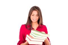 Jeune fille latine tenant la pile des livres image stock