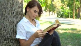 Jeune fille lisant un livre en parc, apprenant le concept banque de vidéos