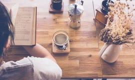 Jeune fille lisant un livre et buvant du café, vue supérieure photo stock