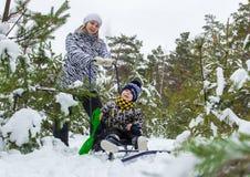 Jeune fille, mère, marchant avec son petit fils dans la forêt d'hiver photo libre de droits