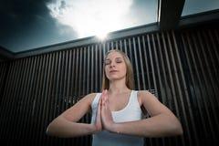 Jeune fille méditant sous la lumière du soleil lumineuse Photographie stock
