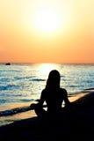Jeune fille méditant sur la plage photographie stock libre de droits