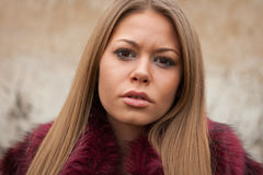 Jeune fille mélancolique avec le manteau de fourrure rouge Photo stock