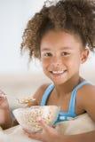 Jeune fille mangeant de la céréale dans la salle de séjour photo libre de droits