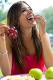 Jeune fille mangeant des raisins sur le pique-nique romantique dans la campagne Image libre de droits