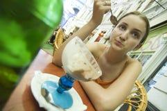 Jeune fille mangeant la crême glacée à l'extérieur Photos libres de droits