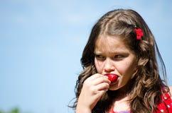 Jeune fille mangeant une fraise fraîche Photographie stock libre de droits