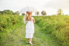 Jeune fille marchant avec le parasol photographie stock