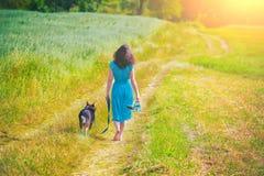 Jeune fille marchant avec un chien Photographie stock