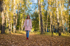 Jeune fille marchant dans la forêt d'automne Photos stock