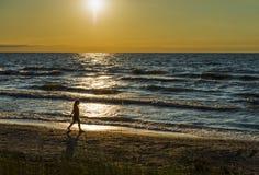 Jeune fille marchant le long de la plage, coucher du soleil d'or Photos stock